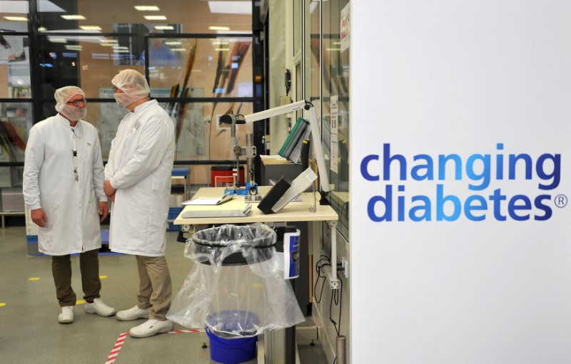Employees stand in the insulin production plant of Danish multinational pharmaceutical company Novo Nordisk in Chartres