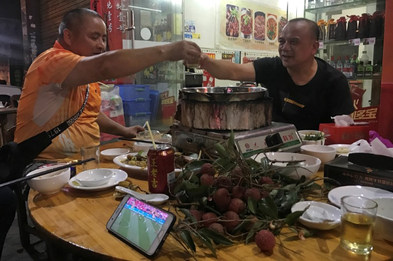 Customers toast as they watching the World Cup 2018 match, over a dog meat dish at a dog meat market ahead of a local dog meat festival in Yulin, Guangxi Autonomous Region