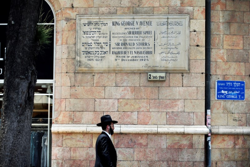 A man walks under a dedication plaque in honor of King George V, in King George street of downtown Jerusalem