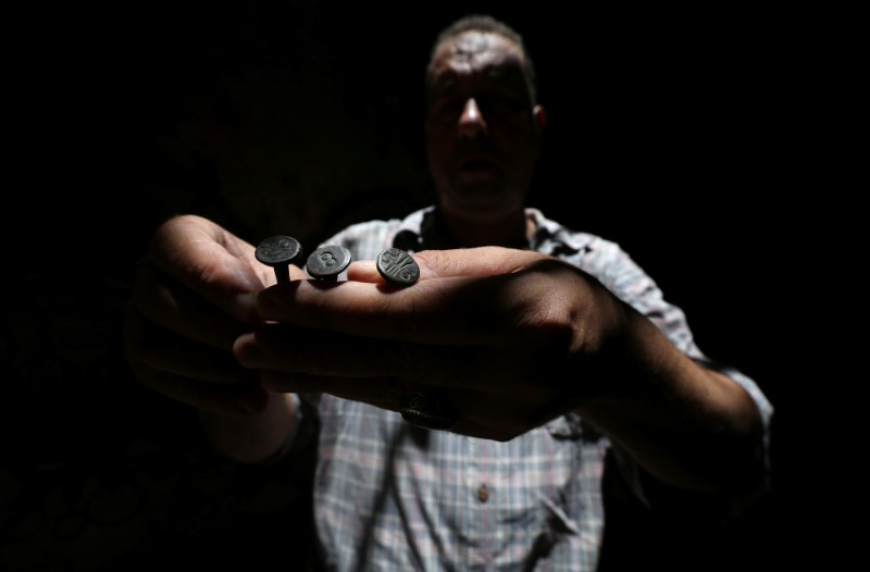 Palestinian carpenter Marwan Shahwan displays what he says are ancient objects from the British era, in Khan Younis in the southern Gaza Strip