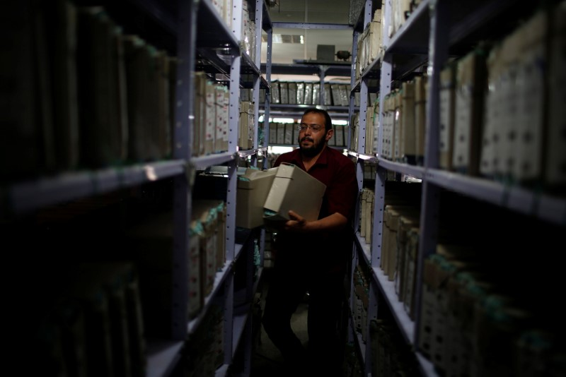 A Palestinian employee carries land registry files at Gaza Land Authority, in Gaza City