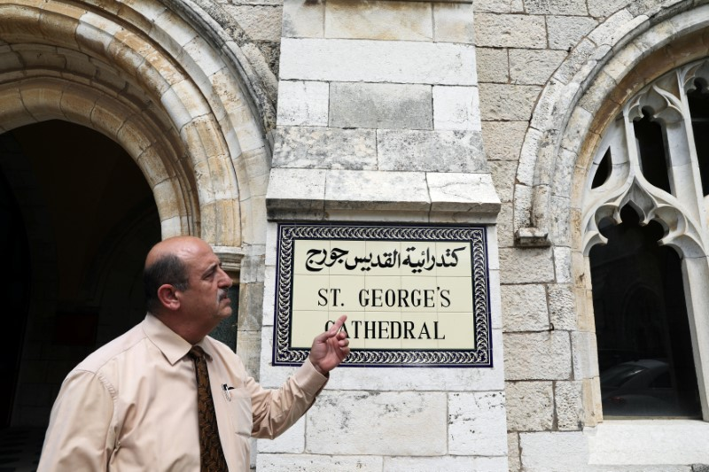 A church official gestures as he stands next to the entrance to the Anglican St. George's Cathedral in Jerusalem