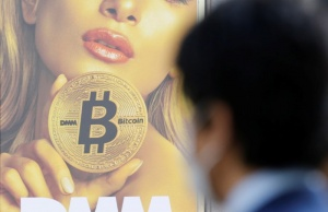 A man stands near an advertisement of a cryptocurrency exchange in Tokyo