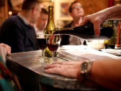 A barman pours a glass of Beaujolais Nouveau wine in a bistrot in Paris