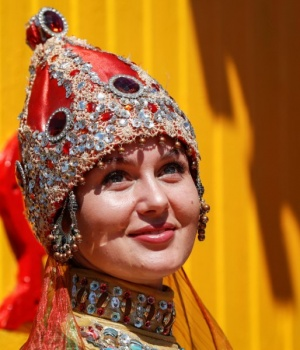 An artist wearing Tatar national outfit looks on at the Sabantuy, a summer festival marking the end of spring crop planting, in Kazan