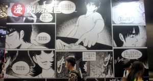 People walk past a booth of NetEase Comics at the CCG Expo in Shanghai