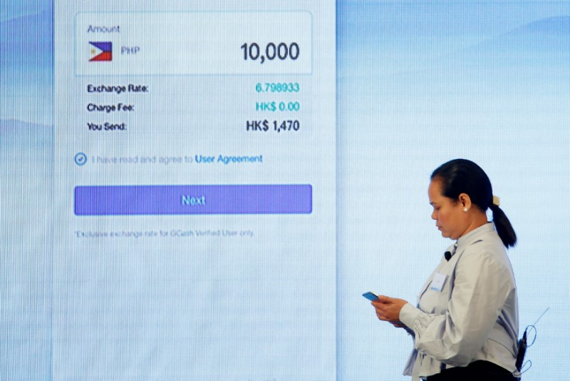 A Filipino guest demonstrates a blockchain-based remittance solution between Hong Kong and the Philippines during a news conference in Hong Kong