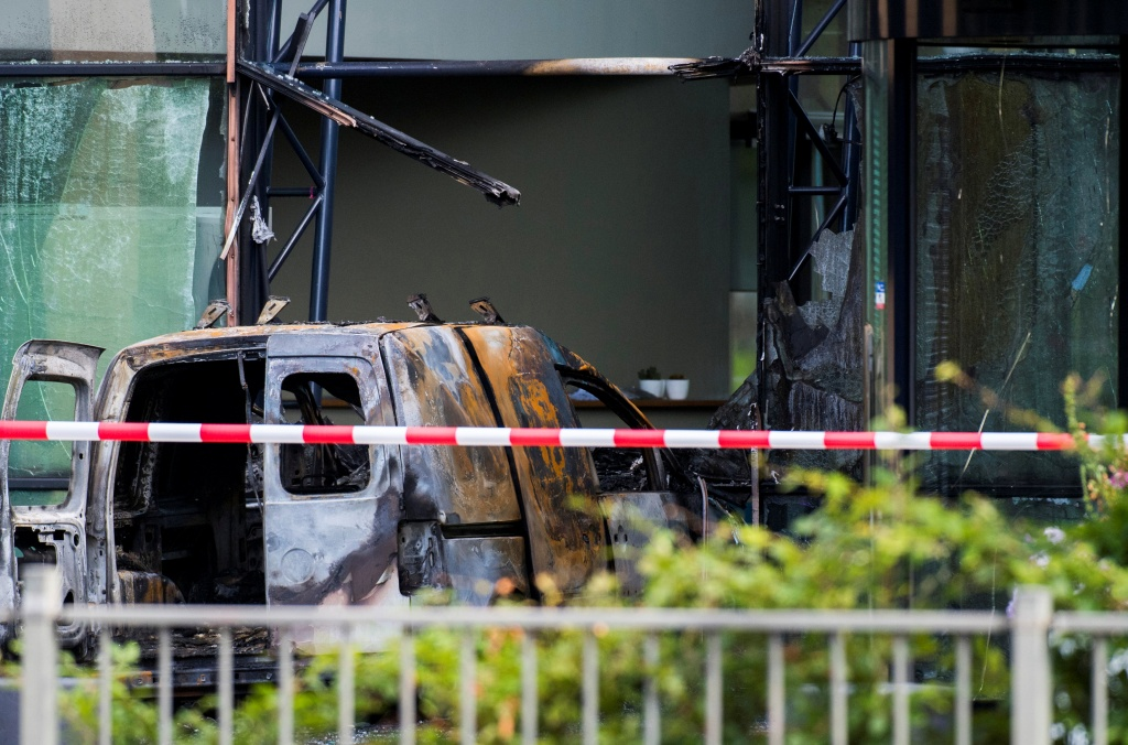 A van is seen burned out after crashing into the glass facade of the head office of Dutch newspaper De Telegraaf in what police said was a deliberate action in Amsterdam