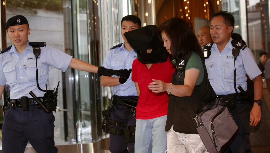A female suspect is arrested by police officers after a woman opened fire and wounded four people at a park outside Taikoo Shing in Hong Kong