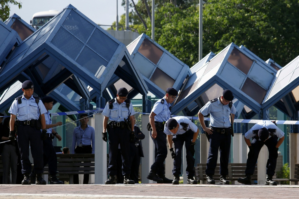 Policemen search the area after open fire in Hong Kong