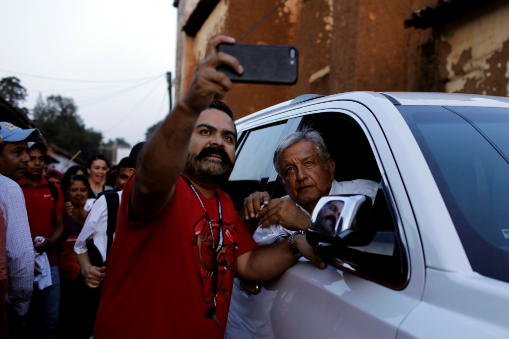 Leftist front-runner Andres Manuel Lopez Obrador of MORENA poses for a selfie with a supporter after a campaign rally in Patzcuaro