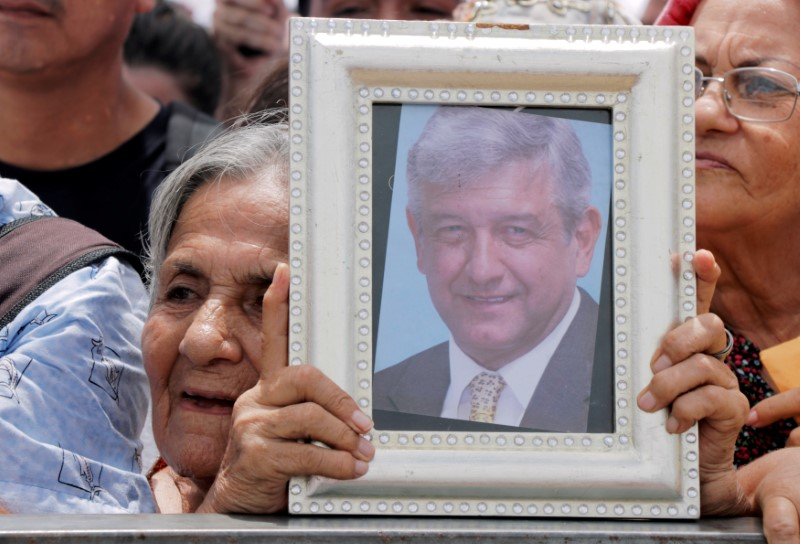 A supporter of Mexican presidential candidate Andres Manuel Lopez Obrador holds a framed photograph of him during a campaign rally, in Cancun