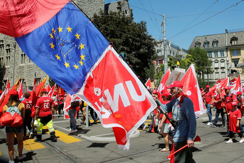 Swiss construction worker carries flags of Swiss workers union Unia and another of the European Union during a demonstration in Zurich