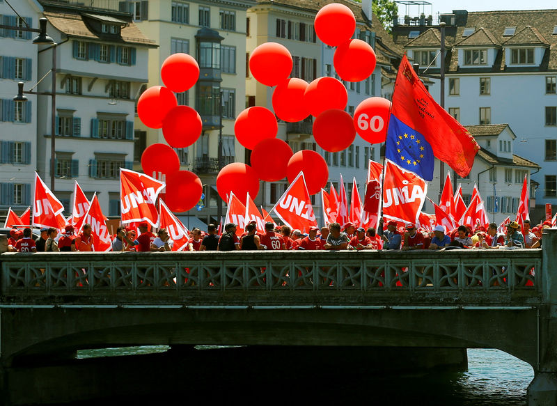Swiss construction workers hold flags of Swiss workers union Unia before a demonstration in Zurich