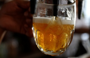 A pint of beer is poured into a glass in a bar in London