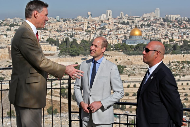 Britain's Prince William speaks to British Consul General in Jerusalem Philip Hall as he stands next to a tour guide during a visit to an observation point on Mount of Olives, overlooking Jerusalem's Old City