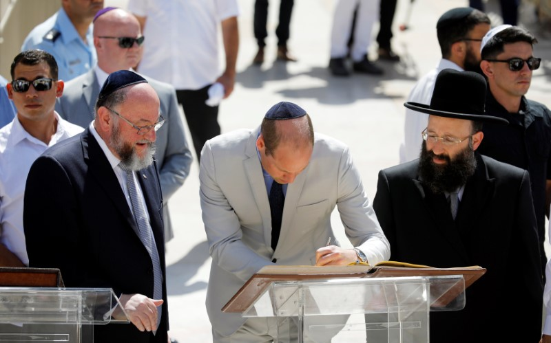 Britain's Prince William signs a guest book as he stands next to Rabbi of the Western Wall Shmuel Rabinovitch during a visit to the Western Wall, Judaism's holiest prayer site, in Jerusalem's Old City