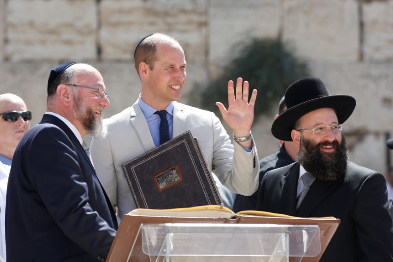 Britain's Prince William waves as he stands with Britain's Chief Rabbi Ephraim Mirvis and Rabbi of the Western Wall Shmuel Rabinovitch during a visit to the Western Wall, Judaism's holiest prayer site, in Jerusalem's Old City