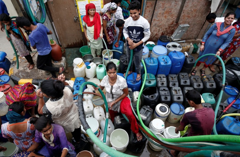 Residents fill their containers with drinking water from a municipal tanker in New Delhi