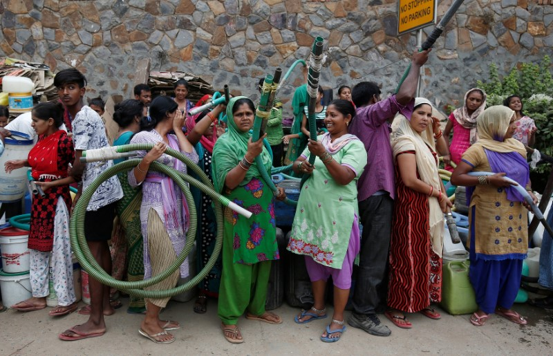 Residents hold hoses as they wait for a municipal water tanker at a colony in New Delhi