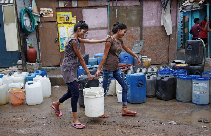 Girls carry a water container after filling it from a municipal tanker in New Delhi