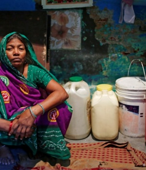 Sushila Devi, whose husband and son died after a brawl with neighbours over water in March, sits next to water containers inside her house in New Delhi