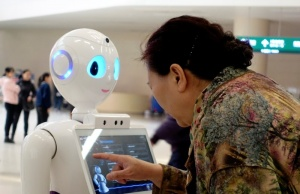 Woman touches a screen on a robot developed by iFlytek at the outpatient hall of a hospital in Beijing