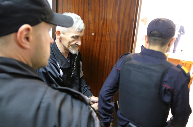 Russian historian Dmitriev is escorted before a court hearing in Petrozavodsk