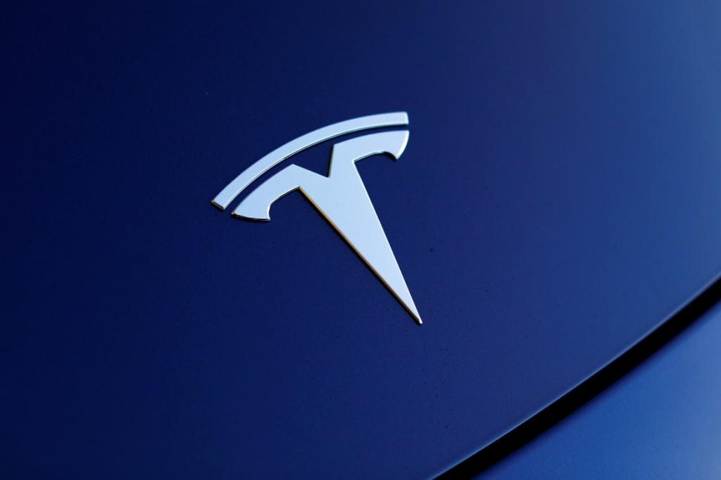 The front hood logo on a 2018 Tesla Model 3 electric vehicle is shown in this photo illustration