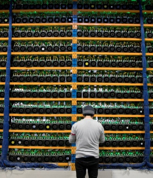 A worker checks the fans on miners, at the cryptocurrency farming operation, Bitfarms,