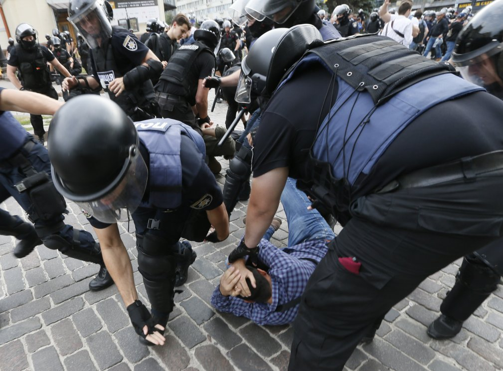 Riot police officers detain anti-LGBT protesters during the Equality March
