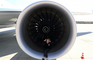 PR agent Elsa Goette sits in a Rolls-Royce engine of an Airbus A350-900 of Ethiopian Airlines during a site-inspection at Fraport airport