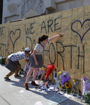 People write messages on construction boarding after a mass shooting on Danforth Avenue in Toronto