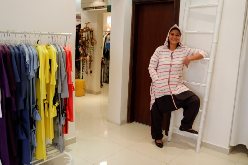 Eman Joharjy, a fashion designer, smiles as she poses in one of her creations at her shop in Jeddah,