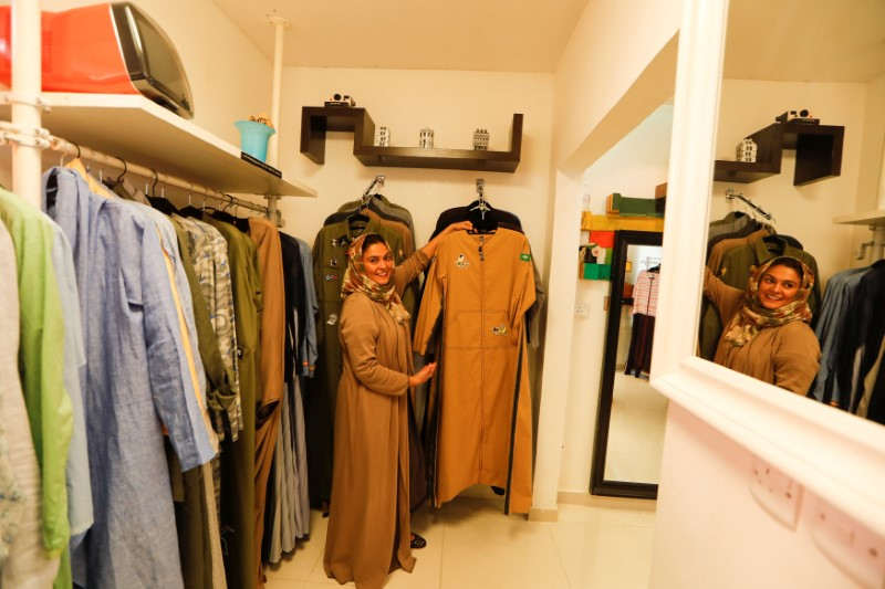 Eman Joharjy, a fashion designer smiles as she shows one of her creations at her shop in Jeddah