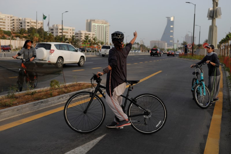 Eman Joharjy, a fashion designer cycles with her friends as they wear her creations along Jeddah's Corniche