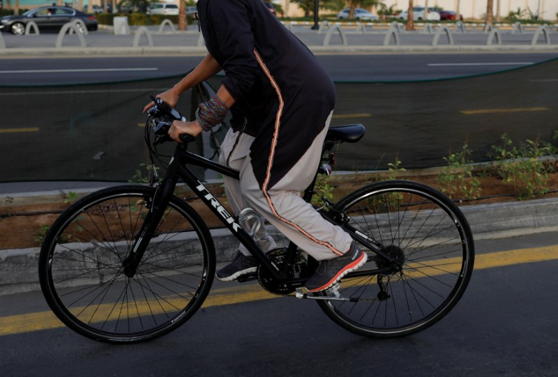 A woman cycles as she wears one of Eman Joharjy's creations along Jeddah's corniche,