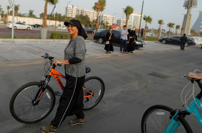 Eman Joharjy, a fashion designer in one of her own creations walks with her bicycle along Jeddah's Corniche