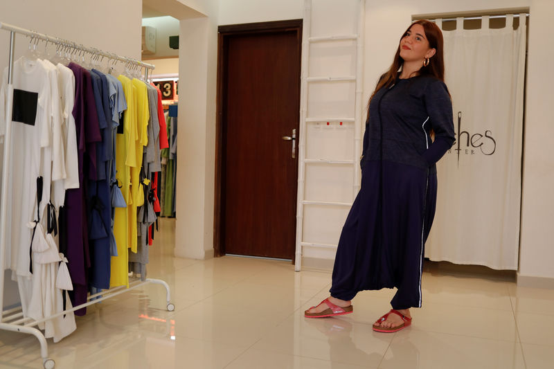 An employee of Eman Joharjy tries on one of Eman's creations at her shop in Jeddah