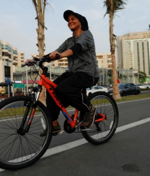 Eman Joharjy, a fashion designer in one of her own creations, cycles along Jaddah's Corniche,