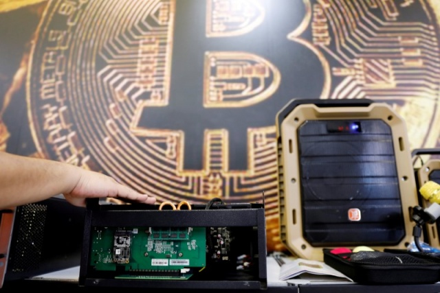 A cryptocurrency mining computer is seen in front of bitcoin logo during the annual Computex computer exhibition in Taipei