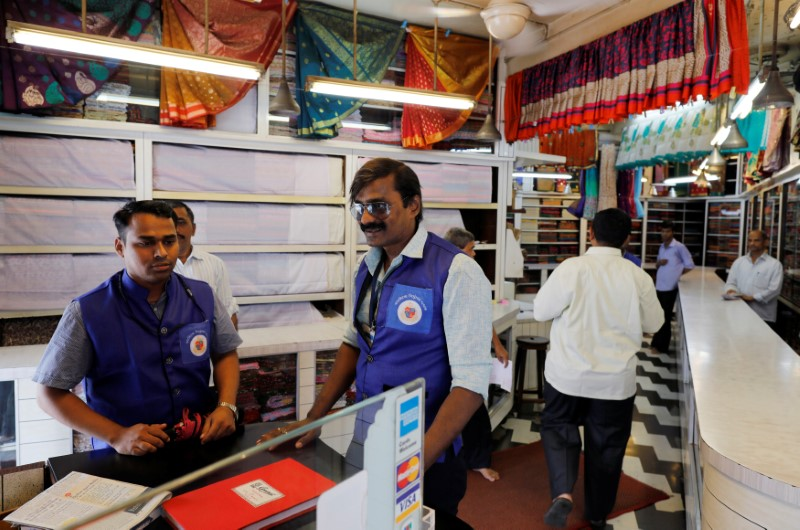 Municipal officers speak to a business owner as others check for plastic bags inside a showroom in Mumbai
