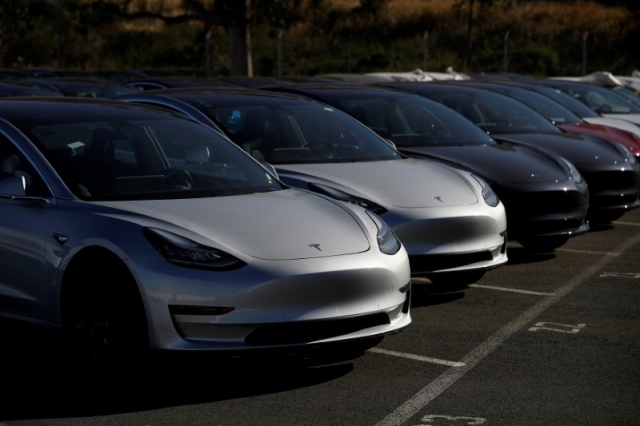 A row of new Tesla Model 3 electric vehicles is seen at a parking lot in Richmond California