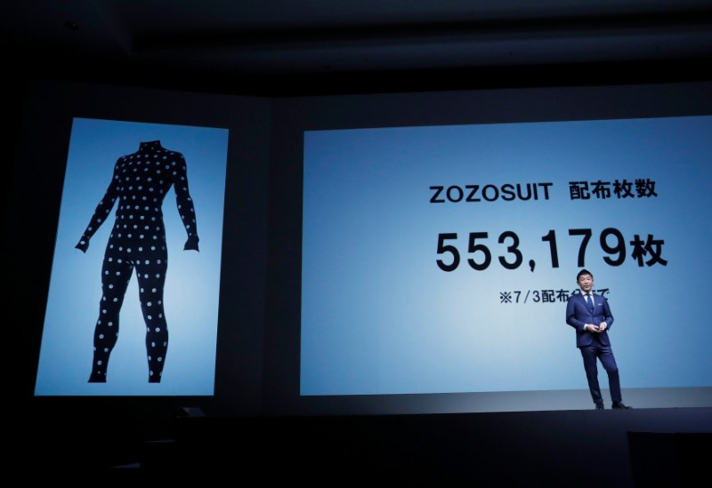 Maezawa, the chief executive of Zozo, which operates Japan's popular fashion shopping site Zozotown, officially called Start Today Co, speaks in front of a projection about Zozosuit at an event launching the debut of its formal apparel items, in Toyko