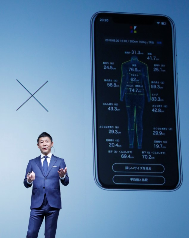 Maezawa, the chief executive of Zozo, which operates Japan's popular fashion shopping site Zozotown, officially called Start Today Co, speaks in front of a projection about Zozosuit at an event launching the debut of its formal apparel items, in Tokyo