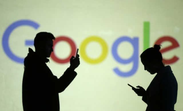 Silhouettes of mobile users are seen next to a screen projection of Google logo in this picture illustration