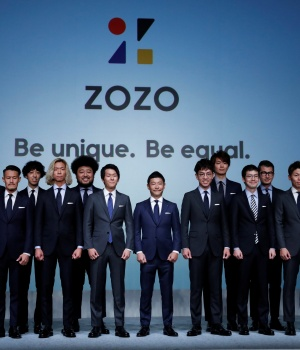 Maezawa, the chief executive of Zozo, which operates Japan's popular fashion shopping site Zozotown, officially called Start Today Co, poses with his employees at an event launching the debut of its formal apparel items, in Tokyo