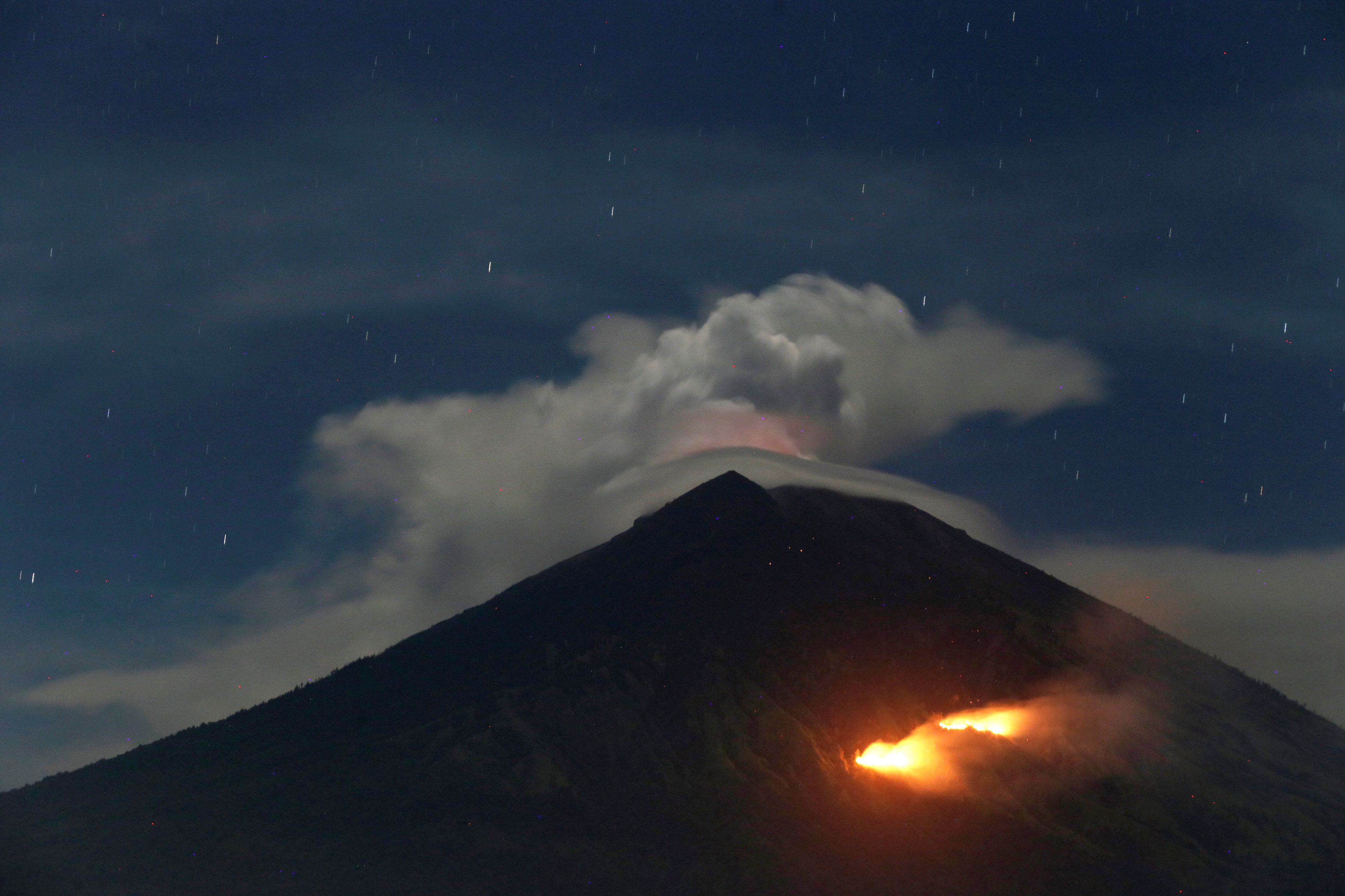 Fire is seen on the slopes of Mount Agung volcano following an eruption as seen from Amed in Karangasem Regency