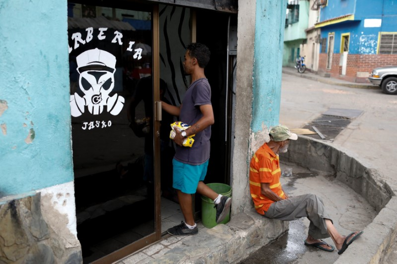 A man enters a barber shop with packages of corn flour in Caracas