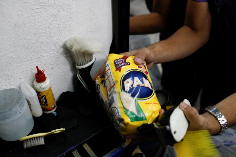 A barber holds a package of corn flour that he get as payment for a haircut in Caracas